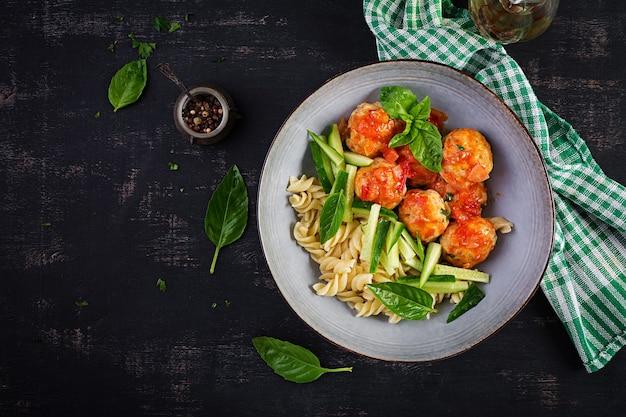 Włoski makaron. fusilli z klopsikami, ogórkiem i bazylią na ciemnym tle. obiad. koncepcja powolnego jedzenia. widok z góry, układ płaski