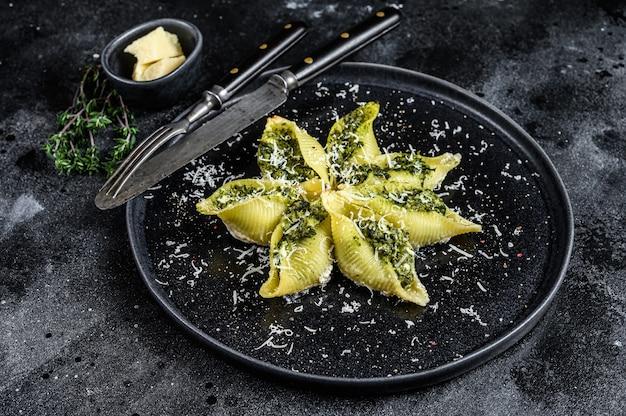 Włoski makaron jumbo muszle conchiglioni faszerowany mięsem wołowym i szpinakiem na talerzu na czarnym stole. widok z góry.