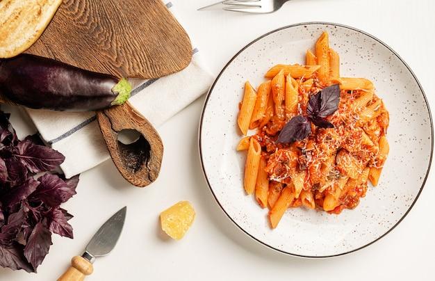 Włoski makaron penne alla norma z bakłażanem, sosem pomidorowym i parmezanem.