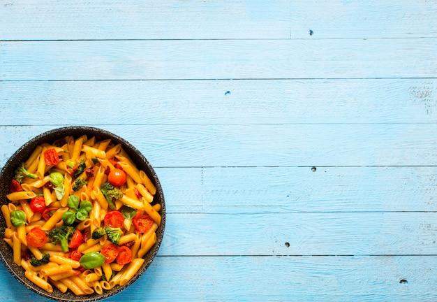 Włoski makaron penne w sosie pomidorowym i różnego rodzaju warzywach, na drewnianym stole