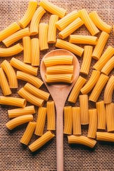 Włoski makaron penne, węglowodany na rustykalnym tle