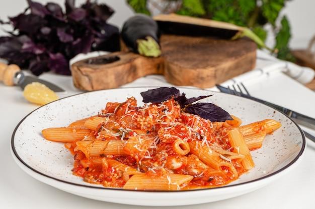 Włoski makaron penne z bakłażanem i sosem pomidorowym.