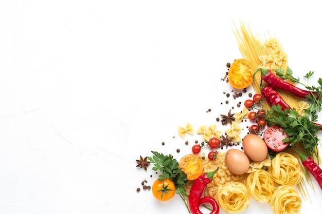 Włoski makaron różnego rodzaju z przyprawami, czerwona ostra papryka, jaja kurze, żółte i czerwone pomidory na białym kamiennym tle. koncepcja gotowania włoskiego makaronu i sosu. leżał płasko, widok z góry