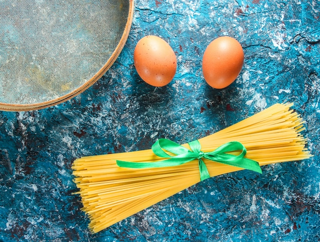 Włoski makaron, sito, jajka na niebieskim betonowym stole. proces gotowania. widok z boku