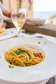 Włoski makaron spaghetti z jeżowca na białym talerzu w rastaurancie