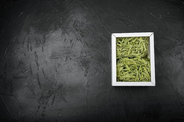 Włoski makaron w zestawie, na czarnym tle ciemnego kamiennego stołu, płaski widok z góry, z miejscem na kopię tekstu