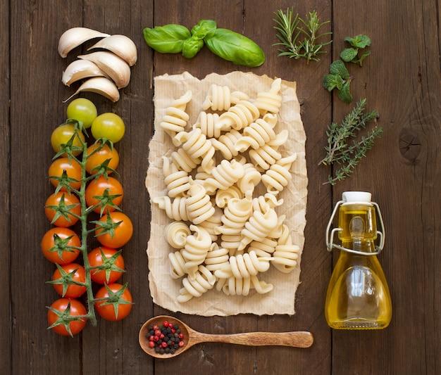 Włoski makaron, warzywa, zioła i oliwa z oliwek na drewnianej powierzchni