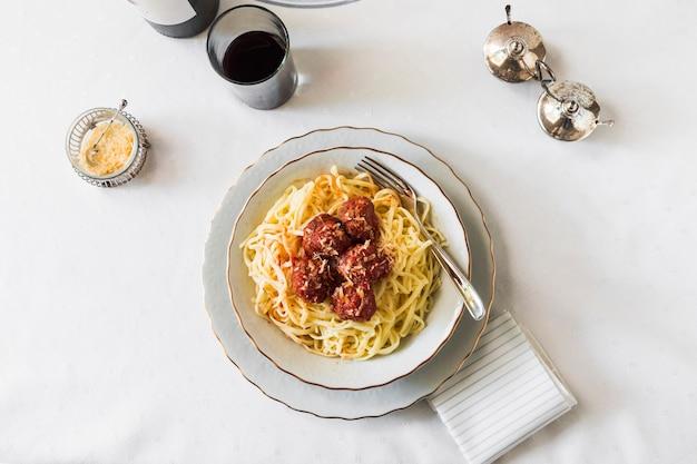 Włoski makaron z klopsikami w białym ceramicznym pucharze