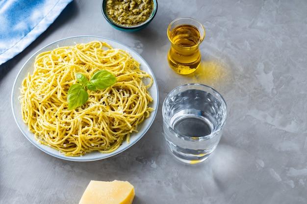 Włoski makaron z sosem pesto i dodatkami. spaghetti z sosem pesto i bazylią