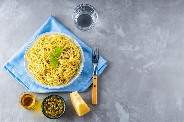 Włoski makaron z sosem pesto i dodatkami. spaghetti z sosem pesto. kuchnia włoska