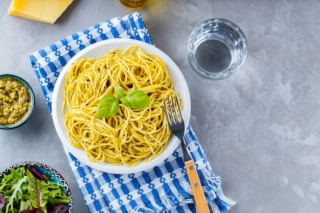 Włoski makaron z sosem pesto i mixem sałat z zieleniny. spaghetti z sosem pesto i świeżą bazylią na szarym tle. skopiuj miejsce. widok z góry