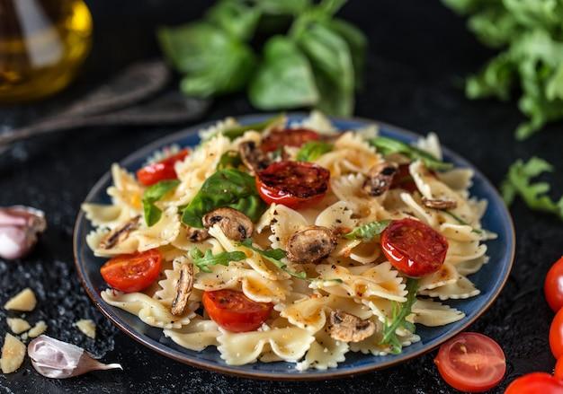Włoski makaron z sosem, pomidorami koktajlowymi, bazylią i parmezanem. pyszny talerz z makaronem