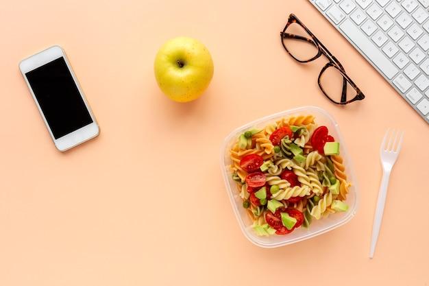 Włoski makaron z warzywami na biurowym biurku z klawiaturą