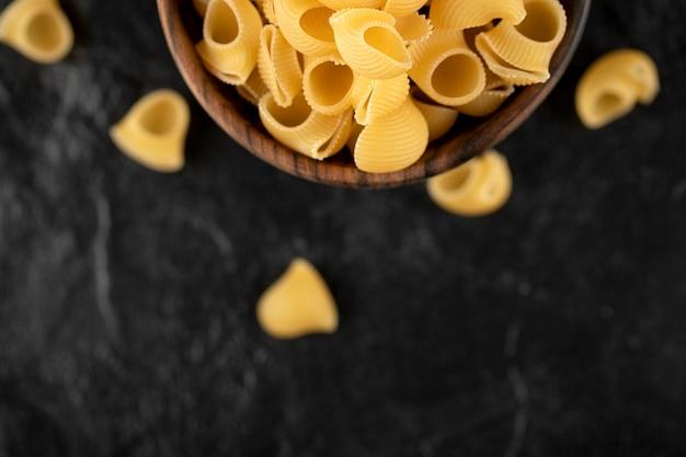 Włoski niegotowany makaron conchiglie w drewnianej misce.