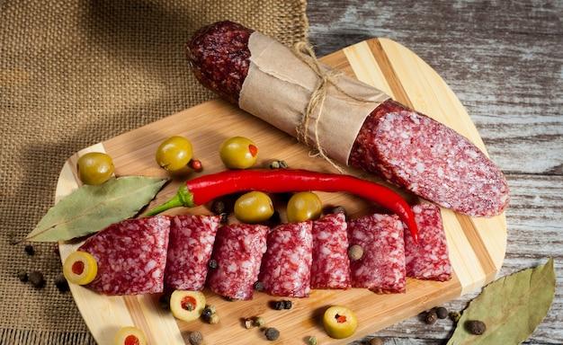Włoski salami z oliwkami i pikantność na drewnianym tle