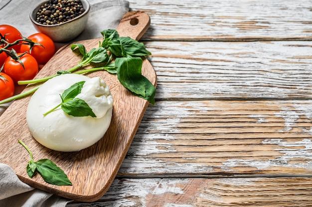 Włoski ser bawełniany burrata z liśćmi bazylii. białe drewniane tła. widok z góry. skopiuj miejsce