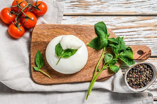 Włoski ser bawełniany burrata z liśćmi bazylii. białe drewniane tła. widok z góry