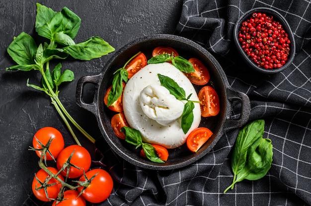 Włoski ser buffalo burrata z liśćmi bazylii i pomidorami