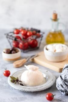 Włoski ser burrata na okrągłym białym talerzu i składniki do sałatki