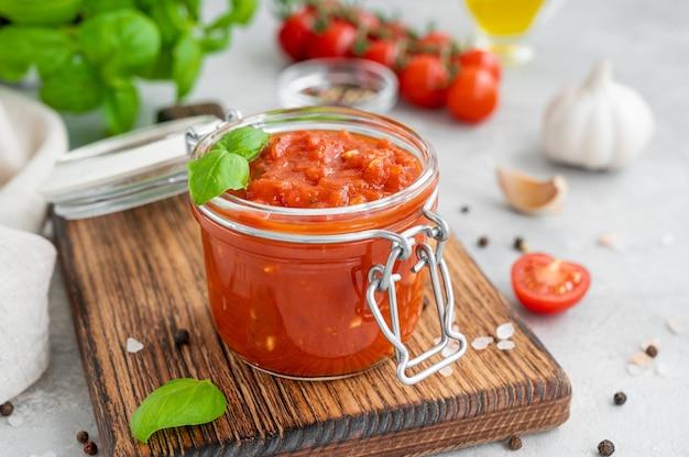Włoski sos marinara w słoiku na betonowym tle z przyprawami i składnikami.