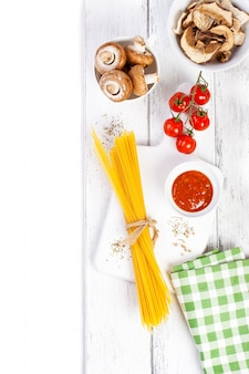 Włoski spaghetti champignon suche grzyby sos pomidorowy wiśni świeżych pomidorów i przyprawy na drewnianym tle makaron składników widok z góry kopi pionowej
