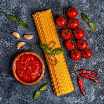 Włoski stół z makaronem, przyprawami i warzywami.
