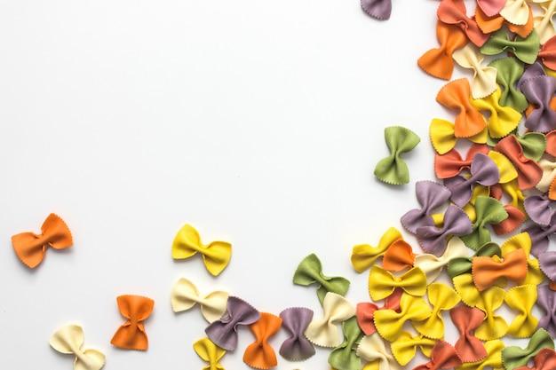 Włoski surowy stubarwny farfalle makaron na białym tle z kopii przestrzenią.