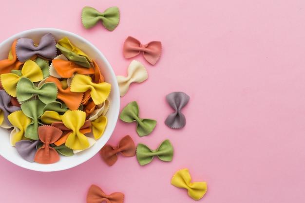 Włoski surowy stubarwny farfalle makaronu zakończenie w pucharze na różowym tle.