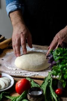 Włoski szef kuchni gotowanie pizzy mężczyzna ręce gotowanie ciasta do pizzy na pizzę