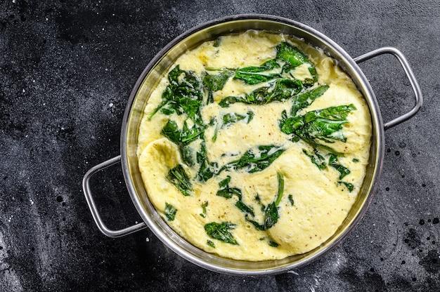 Włoski szpinak i omlet serowy na patelni. czarne tło.
