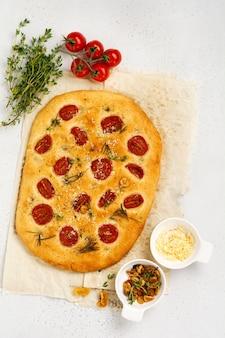 Włoski tradycyjny chleb focaccia zapiekany z pomidorkami koktajlowymi, parmezanem i rozmarynem na jasnobrązowym tle. widok z góry