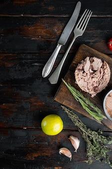 Włoski tuńczyk w puszkach, na drewnianej desce do krojenia, na starym ciemnym tle drewnianego stołu z ziołami i składnikami, widok z góry płaski, z copyspace i miejscem na tekst