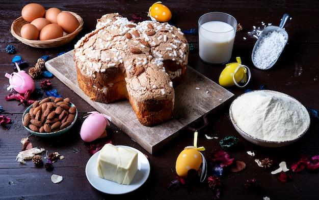 Włoski wielkanocny tort gołąbek (colomba pasquale) i składniki mleko migdałowe jajka na starej rustykalnej drewnianej desce