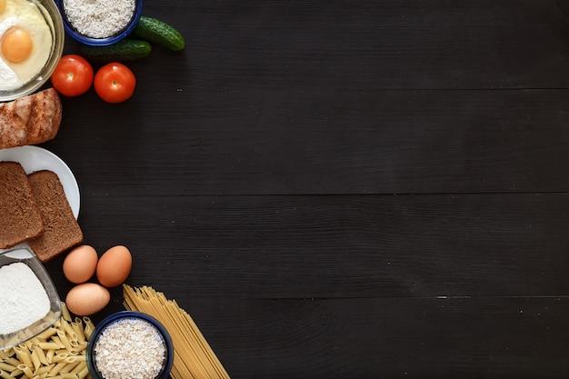 Włoski zdrowy jedzenie stół, spaghetti warzywa na czarnym drewnianym biurku, odgórny widok