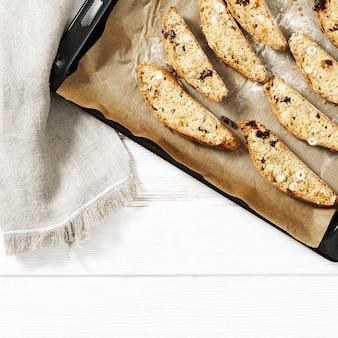 Włoskie ciasteczka biscotti na czarnej blasze do pieczenia i białym stole.