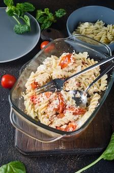 Włoskie danie mieszania makaronu z zapiekanym serem feta i pomidorami na ciemnym tle. fetapasta. trend wirusowy przepis, układ płaski, przestrzeń do kopiowania