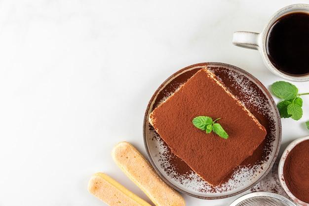 Włoskie domowe ciasto tiramisu ze świeżą miętą na talerzu i filiżanką kawy na białej powierzchni