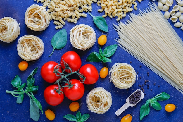 Włoskie jedzenie . kuchnia włoska. składniki pomidory, żółte pomidory czereśniowe, świeża bazylia, odciski czarnego pieprzu, różne makarony.