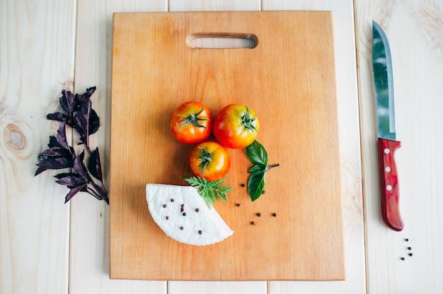Włoskie jedzenie. pomidory bazylia ser na desce
