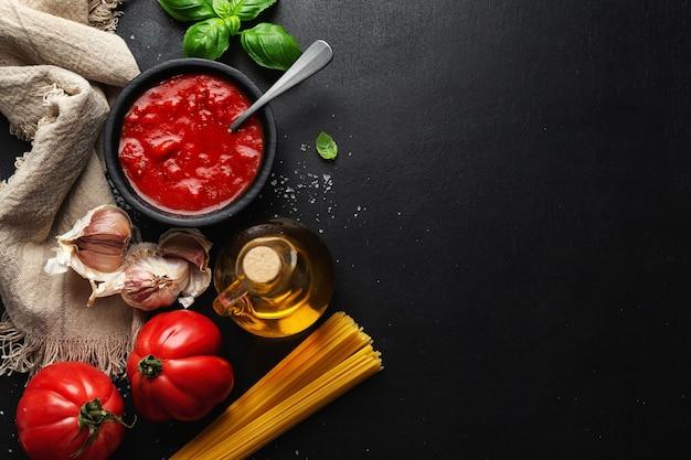 Włoskie jedzenie tło z warzywami spaghetti i sosem pomidorowym na ciemnym stole. widok z góry.