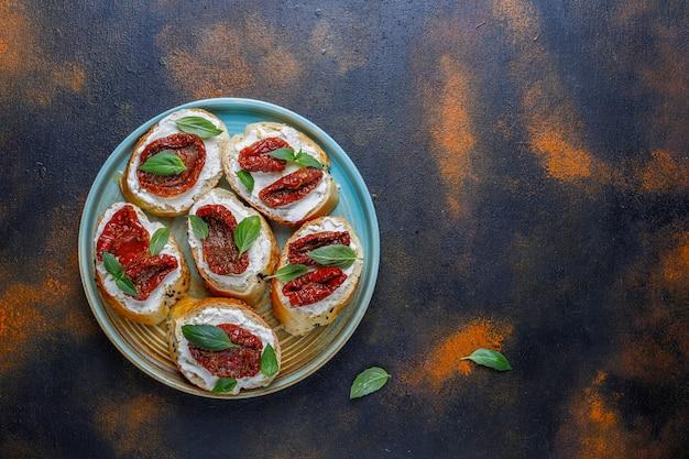 Włoskie kanapki - bruschetta z serem, suszonymi pomidorami i bazylią.