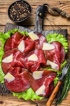 Włoskie mięso antipasti bresaola pokrojone z zieloną sałatą i parmezanem. drewniane tła. widok z góry.