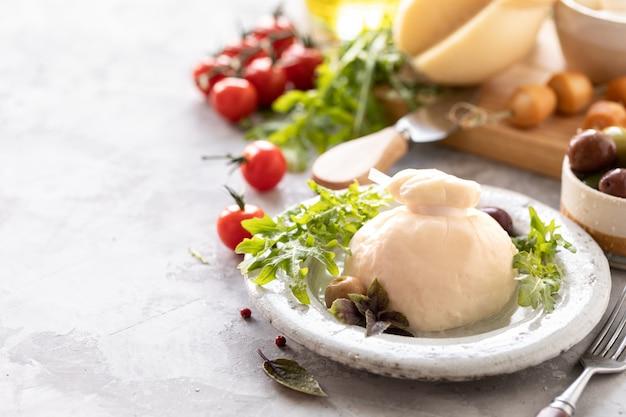 Włoskie sery burrata, mozzarella, scorocia, boccini z oliwkami, pomidorami koktajlowymi i rukolą na okrągłym białym talerzu na jasnym tle. skopiuj miejsce