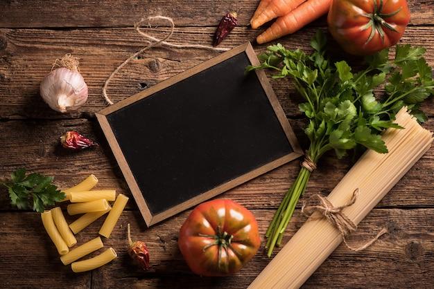 Włoskie składniki do gotowania żywności. makaron, warzywa. widok z góry z miejscem na kopię