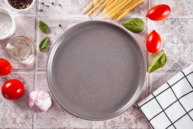 Włoskie składniki makaronu na stole z pustym talerzem. gotowanie żywności. widok z góry. skopiuj miejsce.