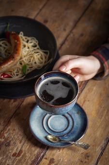 Włoskie spaghetti z makaronem, smażona kiełbasa mięsna na czarnej patelni