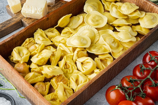 Włoskie surowe ręcznie robione ravioli ze świeżymi składnikami, bazylią, pesto, szynką, serem mozzarella, parmezanem, w drewnianym pudełku, na szarym tle