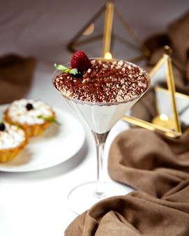 Włoskie tiramisu w kieliszku koktajlowym zwieńczone posypką z kawy i truskawką