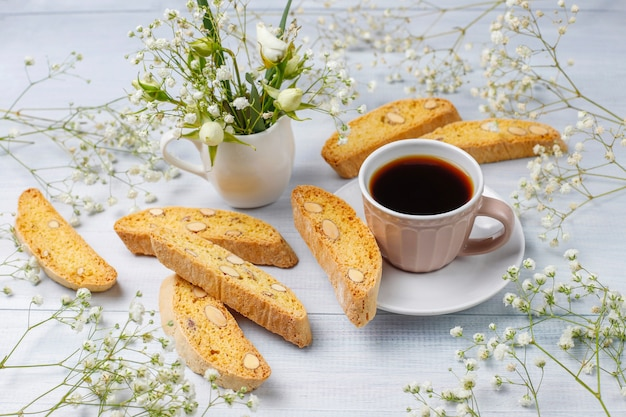 Włoskie tradycyjne toskańskie ciasteczka cantuccini z migdałami, filiżanka kawy na świetle