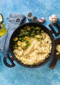 Włoskie wiosenne risotto z brukselką i parmezanem na stole.